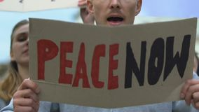 Protesters with banners shouting Peace now, anti-war movement, against terrorism. Stock footage stock video