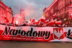 Independence Day March in Warsaw Poland Marred by Violence and Controversy. Protesters follow a banner up the road as they set off flares and wave banners at the Royalty Free Stock Photography