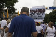 Protesters participating in the event called The mother of all protests in Venezuela against Nicolas Maduro government. With a board that reads assassin Royalty Free Stock Photography