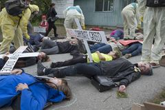 Kinder Morgan protesters stage a die-in at the Kinder Morgan tank farm on Burnaby Mountain, BC. Kinder Morgan protesters play dead in a die in on May 16 to royalty free stock photography