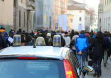 Protesters rioting during a protest in the street and the police. Car of the escorting stock photos