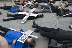 Kinder Morgan protesters stage a die-in at the the tank farm on Burnaby Mountain, BC. Kinder Morgan protesters play dead in a die-in on May 16 to illustrate the royalty free stock photos