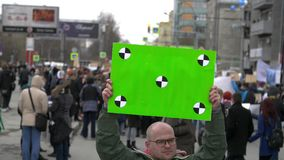 Protesters are on the street in the city. Serious adult young man with a green banner in hands. stock footage