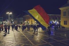 Protestierender, der rumänische Flagge wellenartig bewegt Stockbild