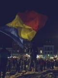 Protestierender, der rumänische Flagge wellenartig bewegt Stockbilder