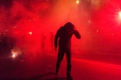 Protestierender, der weg von Rauche sich versteckt Stockfotografie
