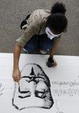 Protestor paonts weiße Maske auf Fahne Stockbild