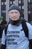 Protestor with Putin's mask. MOSCOW - DECEMBER 24: The protester with Putin's mask on his face and inscription on his t-shirt: I am ready to work as a President Royalty Free Stock Photography