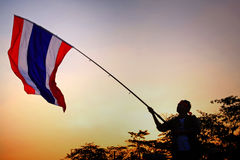 Protestor raises Thai flag at twilight. BANGKOK-JAN 13: Unidentified protestor raises Thai flag at Ladprao junction to anti government and ask to reform before Stock Photo