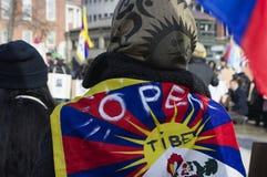 Protestor wearing Tibet flag. Boston, Massachusetts USA - March 2013 - Man wearing tibet flag on shoulders during the Boston Free Tibet march through the Boston Royalty Free Stock Image