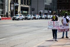 Protestors Hold Signs as a Fleet of Police Cars Drives Past