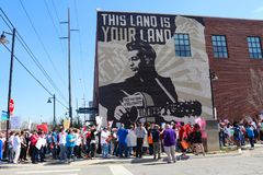Protestors march by Woody Guthrie Mural that says This Machine Kills Fascists at March for Life protest in Tulsa Oklahoma 2 24 201. Protestors march by the Woody stock photography