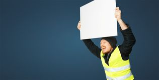 Protests yellow vests. Young man is holding poster. Concept of revolution and protest on blue background stock photo