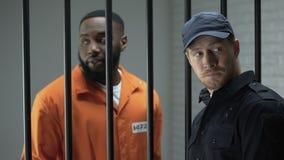Protetor de cadeia que dá o pacote afro-americano com comprimidos, atividade ilegal do prisioneiro filme
