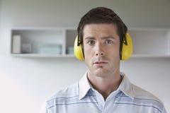 Protetores auriculares vestindo do homem no escritório Fotografia de Stock Royalty Free