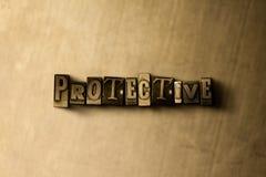 PROTETTIVO - il primo piano dell'annata grungy ha composto la parola sul contesto del metallo fotografia stock