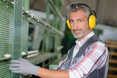 Protezione acustica d'uso del lavoratore alla fabbrica immagine stock