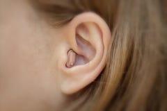 Prothèse auditive en votre plan rapproché d'oreille photographie stock libre de droits