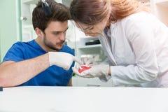 Prothèse dentaire, dentiers, travail de prosthétique Mains de prosthétique tout en travaillant au dentier, aux dents fausses, à u Photographie stock