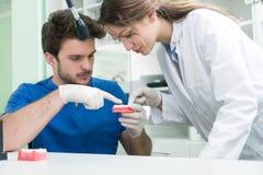 Prothèse dentaire, dentiers, travail de prosthétique Mains de prosthétique tout en travaillant au dentier, aux dents fausses, à u Photo stock