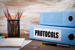 Protocols, Office Binder on Wooden Desk. On the table colored pe. Ncils, pen, notebook paper royalty free stock photo