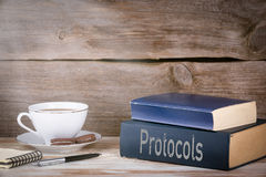 Protocols. Stack of books on wooden desk Stock Photo