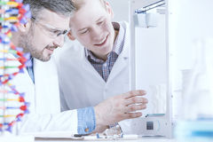 Prototype of modern printer. Two scientists testing prototype of modern printer Stock Images