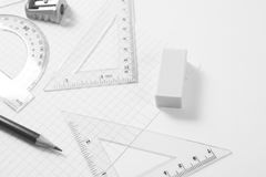 Protractor, rulers, pencil and eraser on squared paper Stock Images