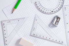 Protractor, rulers, pencil and eraser on squared paper Royalty Free Stock Photography
