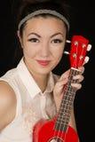 Protrait adolescente de la muchacha de Amerian del asiático con un ukelele rojo Foto de archivo