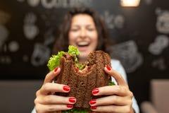 Protrait borrado engraçado do close up do sanduíche mordido posse da jovem mulher por suas duas mãos Sanduíche no foco Fundo escu fotografia de stock royalty free