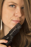 Protrait of a brunette woman peering over a black gun Stock Photography