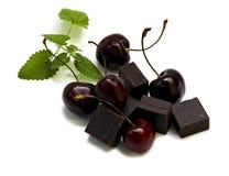 Protuberância preta do chocolate e grande cereja escura isoladas no branco imagens de stock
