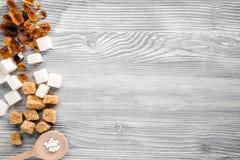 Protuberâncias de açúcar nas colheres no espaço cinzento da opinião superior do fundo da tabela para o texto Fotos de Stock