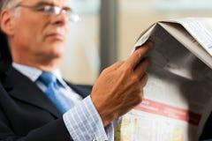 Protuberancia en su periódico de la lectura de la oficina Imagen de archivo libre de regalías