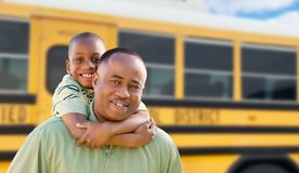 African American Dad and Son Piggyback Near School Bus royalty free stock images