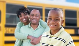 Proud African American Parents and Young Boy Near School Bus stock images