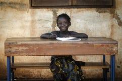 Proud African Schoolgirl Sitting In Her Desk Smiling school bac. School Background: Proud African Schoolgirl Sitting In Her Desk Smiling Royalty Free Stock Photo