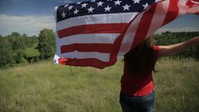 Proud american girl holding stars and stripes in slow motion stock video footage