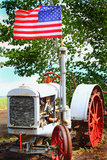 Proud American Roots. An American flag and an old McCormick Deering hand crank farm tractor sits in a field Royalty Free Stock Photography