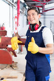 Proud Asian carpenter showing thumbs up Royalty Free Stock Photo