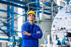 Proud Asian worker in production factory. Proud Asian worker standing in production factory Royalty Free Stock Image