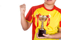 Proud athlete gestures with firm fist whilst holding gold trophy Stock Image