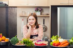 Proud attractive asian female cook standing in her home kitchen. And smiling at camera, with various vegetables and fruits on the counter top, classice vintage royalty free stock image