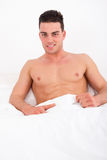Proud attractive man lying in bed with naked torso smiling Royalty Free Stock Image