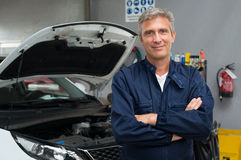 Proud Auto Mechanic. Portrait Of Satisfied Auto Mechanic With Arm Crossed In Garage Royalty Free Stock Images