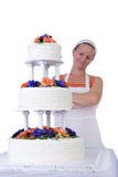 Proud Baker Lady Checking her Ruffled Wedding Cake. Baker lady giving to a wedding cake latest proud look in her apron and white bandanna, cake has fondant Royalty Free Stock Images