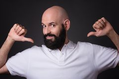Proud bald and beared man confident pose. Portrait of a confident bearded man pointing fingers at himself isolated over dark background Stock Photo