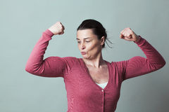 Proud beautiful 40s woman admiring her flexing muscles Stock Photos