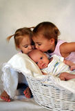 Proud Big Sisters. Two big sisters kiss their new baby brother on the head while he sits in a baskets Royalty Free Stock Photography